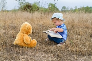 child reading to stuffed animal