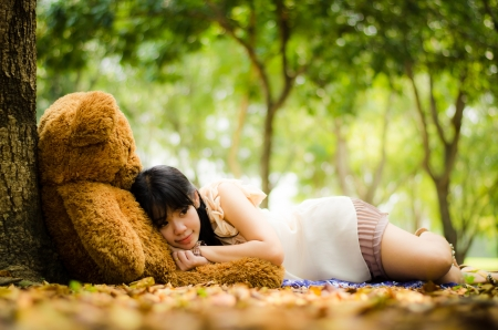girl resting under a tree with a teddy bear