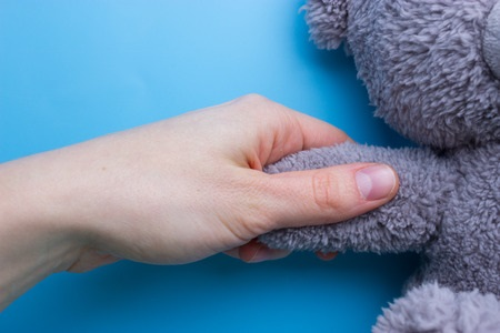 girl hands holding a teddy bear