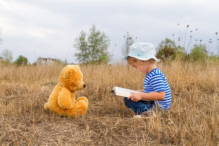 girl reading book teddy bear