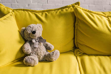 stuffed bear on yellow couch