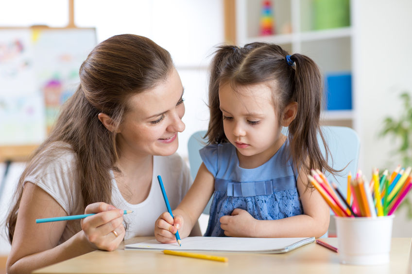 babysitter helping child color a drawing